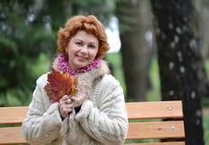 Retrato da mulher alegre dos anos médios com as folhas de bordo do outono nas mãos Foto de Stock Royalty Free