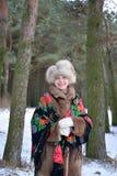 Retrato da mulher alegre dos anos médios na madeira de pinho do inverno Imagens de Stock