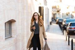 Retrato da mulher alegre que bebe o café afastado ao andar através da rua da cidade imagem de stock