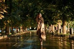Retrato da mulher alegre que usa o telefone celular ao andar através da aleia vazia fotografia de stock royalty free
