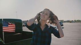 Retrato da mulher americana de sorriso bonita nova com o cabelo do voo que levanta no parque de estacionamento perto do movimento video estoque
