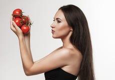 Retrato da mulher apta dos jovens que guarda tomates vermelhos lustrosos Foto de Stock Royalty Free
