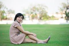 Retrato da mulher asiática bonita no relaxamento do parque exterior com sorriso feliz Fotografia de Stock