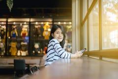 Retrato da mulher asiática bonita que sorri e que olha a câmera no café da cafetaria, feliz e fresco com pensamento positivo foto de stock