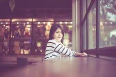 Retrato da mulher asiática bonita que sorri e que olha a câmera no café da cafetaria, feliz e fresco com pensamento positivo, vin fotos de stock royalty free