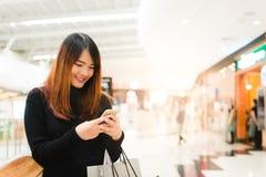 Retrato da mulher asiática nova bonita no shopping, sorrindo usando o telefone esperto à rede dentro fotografia de stock
