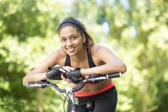 Retrato da mulher atlética latin de sorriso bonita com bicicleta, OU fotografia de stock