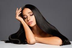 Retrato da mulher atrativa com o cabelo reto que coloca na tabela Fotos de Stock Royalty Free