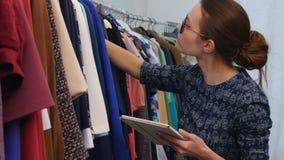 Retrato da mulher atrativa do proprietário de loja da roupa que guarda a tabuleta digital em suas mãos e que trabalha na loja video estoque