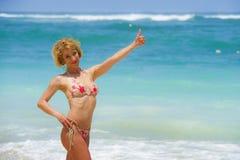 Retrato da mulher atrativa e feliz nova no biquini que levanta em surpreender a praia bonita do deserto que dá o polegar acima de fotos de stock