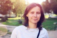 Retrato da mulher atrativa nova de sorriso em exterior Menina moreno caucasiano no parque do verão Fotografia de Stock Royalty Free