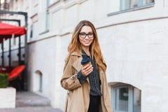 Retrato da mulher atrativa que bebe o café afastado ao andar através da rua da cidade imagens de stock