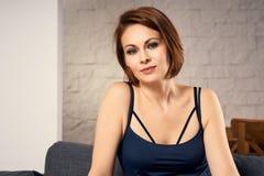 Retrato da mulher atrativa que senta-se no sofá Fotografia de Stock