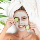 Retrato da mulher da beleza que coloca com a toalha na cabeça, pepino em seus olhos, máscara facial Terapia dos termas relaxe fotografia de stock