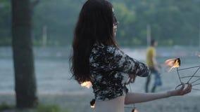 Retrato da mulher da benevolência na máscara que executa uma mostra com a posição da chama no riverbank na frente das árvores Fir vídeos de arquivo