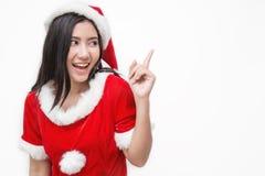 Retrato da mulher bonita asiática que veste o custume de Santa com seu ponto do dedo acima Imagem de Stock
