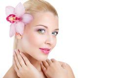 Retrato da mulher bonita com a flor da orquídea em seu cabelo. Woman Face modelo bonito. Pele perfeita. Make-up.Makeup profissiona foto de stock