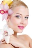 Retrato da mulher bonita com a flor da orquídea em seu cabelo. Woman Face modelo bonito. Pele perfeita. Make-up.Makeup profissiona Fotos de Stock Royalty Free