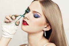 Retrato da mulher bonita com os olhos fechados que guardam o encrespador da pestana Imagem de Stock Royalty Free