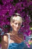 Retrato da mulher bonita de encontro às flores cor-de-rosa Imagens de Stock Royalty Free