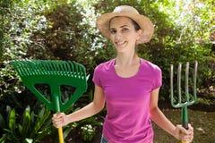 Retrato da mulher bonita de sorriso que guarda a forquilha e o ancinho de jardinagem Imagem de Stock Royalty Free