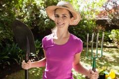 Retrato da mulher bonita de sorriso que guarda a forquilha e a pá de jardinagem Imagem de Stock