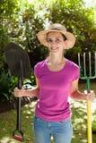 Retrato da mulher bonita de sorriso que guarda a pá e a forquilha de jardinagem Fotografia de Stock Royalty Free