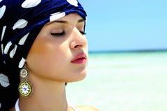 Retrato da mulher bonita em um xaile azul na praia. estilo árabe Fotografia de Stock Royalty Free