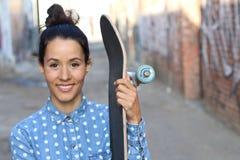 Retrato da mulher bonita feliz com cabelo longo em uma camisa vestindo e em guardar da sarja de Nimes do bolo seu skate que sorri imagem de stock royalty free