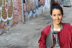 Retrato da mulher bonita feliz com cabelo saudável 'sexy' longo no revestimento vermelho do bombardeiro que guarda seu skate que  imagens de stock