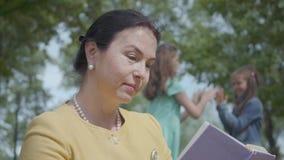 Retrato da mulher bonita madura bonito que l? um livro e suas netas ador?veis para jogar junto no parque no filme