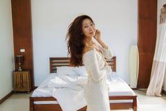 Retrato da mulher bonita na cama no quarto imagem de stock