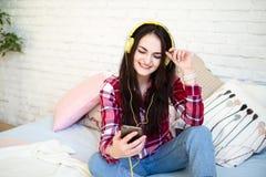 Retrato da mulher bonita na música de escuta da manhã que senta-se na cama em casa Fotografia de Stock Royalty Free