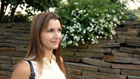 Retrato da mulher bonita na perspectiva de uma parede das pedras e das flores mulher que anda na pedra video estoque