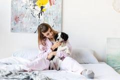 retrato da mulher bonita nos pijamas que guardam pouco cachorrinho ao descansar na cama foto de stock