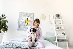 retrato da mulher bonita nos pijamas que guardam pouco cachorrinho ao descansar na cama imagens de stock royalty free