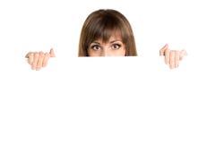 Retrato da mulher bonita nova atrás da placa vazia branca Imagem de Stock Royalty Free