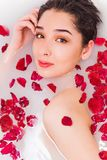 Retrato da mulher bonita nova com flores e as pétalas cor-de-rosa vermelhas no banho da espuma fotos de stock royalty free