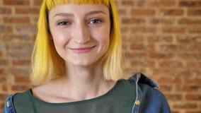 Retrato da mulher bonita nova com o cabelo amarelo que olha a câmera e que sorri, o fundo da parede de tijolo, os felizes e filme