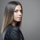 Retrato da mulher bonita nova com o penteado reto do ombre que olha a câmera sobre o ombro Fotografia de Stock