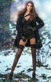 Retrato da mulher bonita nova exterior no cenário do inverno Morena sensual com pés longos no levantamento preto das meias elegan Imagens de Stock