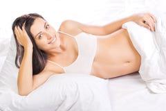 Retrato da mulher bonita nova na cama Fotografia de Stock Royalty Free