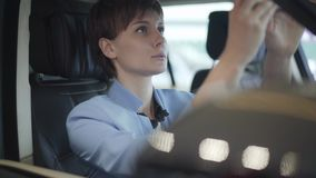 Retrato da mulher bonita nova no terno azul do vestuário formal que senta-se dentro do carro no assento dianteiro do passanger Me filme