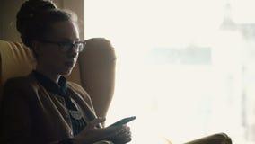 Retrato da mulher bonita nova nos vidros que sentam-se perto da janela e que usam o smartphone para surfar o Internet filme