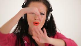 Retrato da mulher bonita nova que escuta vídeos de arquivo