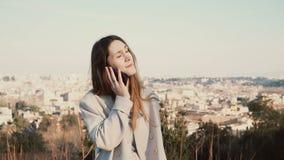 Retrato da mulher bonita nova que está na vista panorâmica de Roma, Itália Fala fêmea no smartphone imagem de stock royalty free