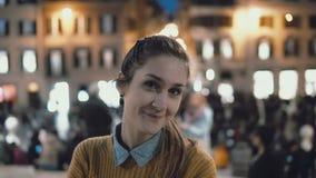 Retrato da mulher bonita nova que está no centro de cidade na noite A menina do estudante olha a câmera, sorrindo imagens de stock royalty free