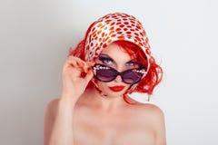 Retrato da mulher bonita nova que levanta com os óculos de sol florais no estúdio fotografia de stock