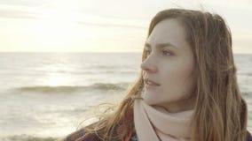 Retrato da mulher bonita nova que olha na distância na costa do mar Posição fêmea na praia no dia frio vídeos de arquivo