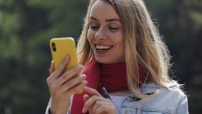 Retrato da mulher bonita nova que veste no lenço vermelho usando o smartphone, verificando o telefone e comemorando a boa notícia video estoque